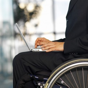 Businessman Sitting in a Wheelchair Working in a Laptop
